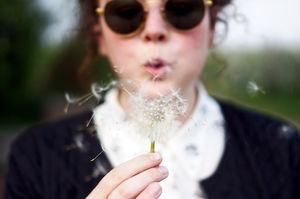 Woman blowing dandelion fluff