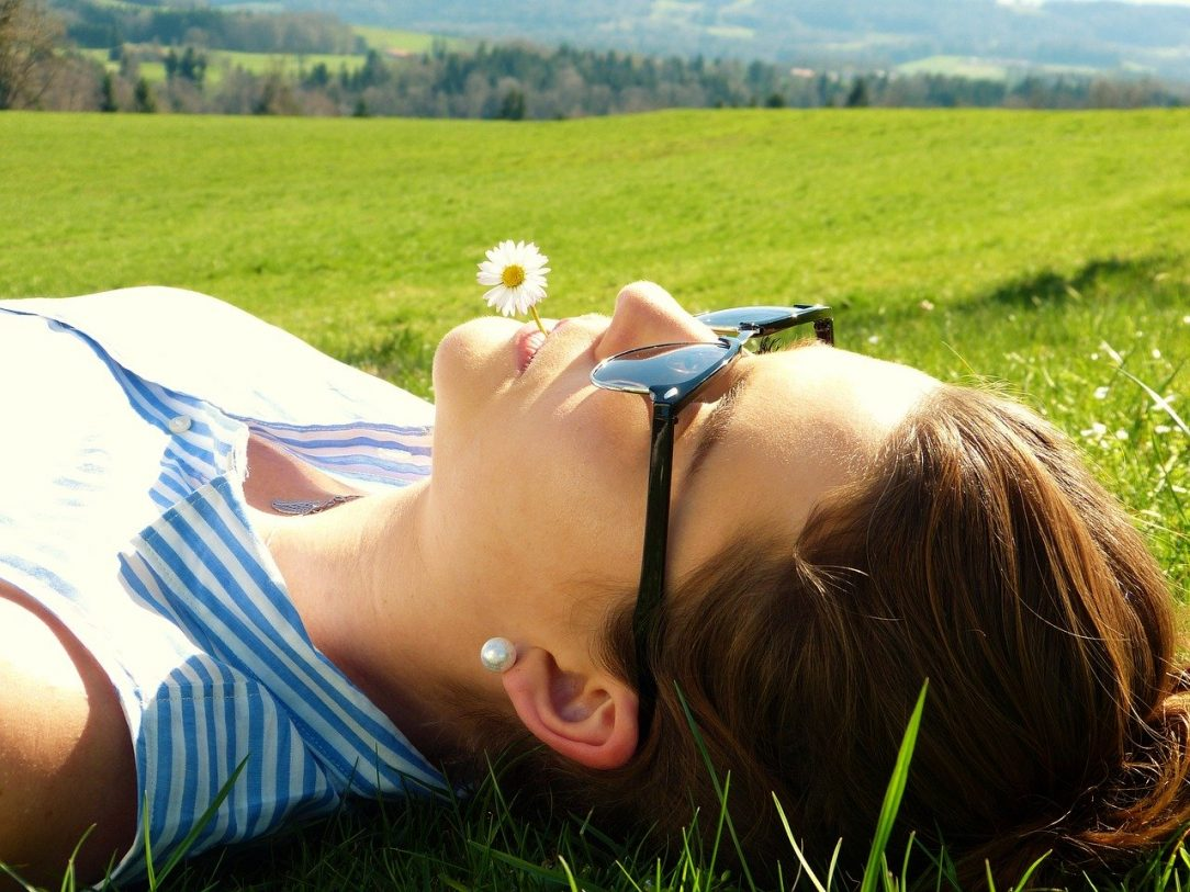 Woman in Grass with Daisy in mouth - learning Meditation