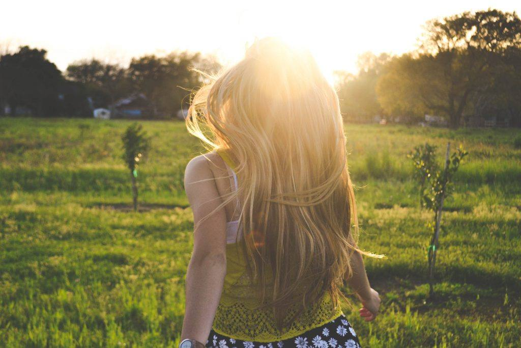 Blond woman walking into sun away from alcohol lies