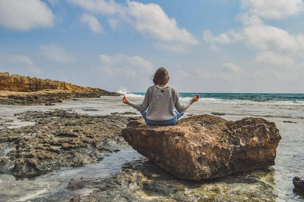Photo of a woman meditating on a rock near the ocean to represent the serenity that meditation can offer a newly sober person
