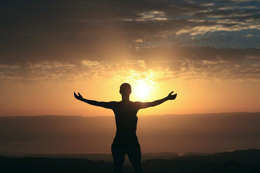 Photo of a person standing on a mountain facing a sunset to represent gaining confidence in sobriety.