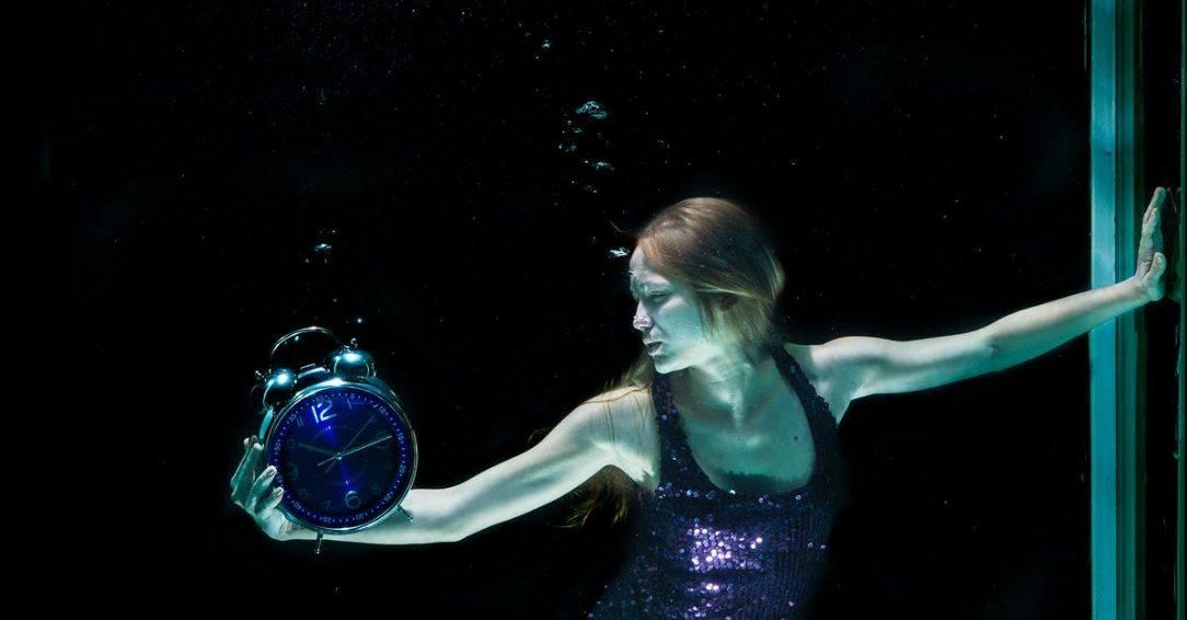Woman underwater with alarm clock alcohol and anxiety