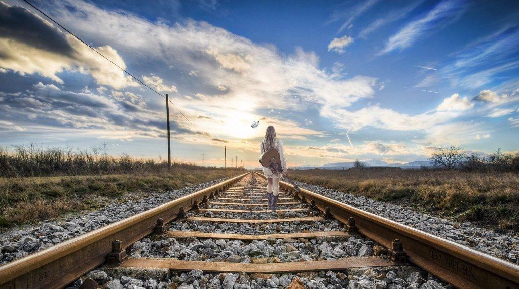 Woman walking away on train tracks- sober journey