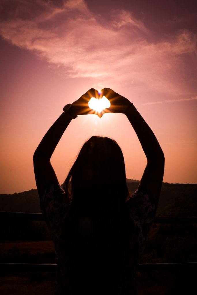 Woman with hands forming heart at Sunset- 3 months sober sprituality