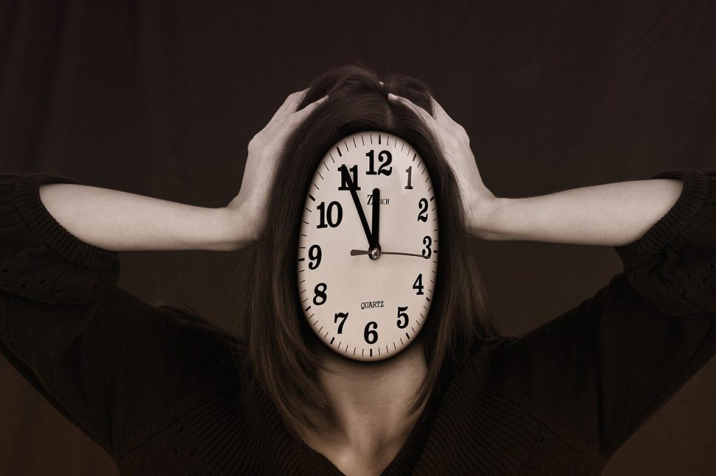 Woman with hands on Head Clock face Burnout in Early Sobriety