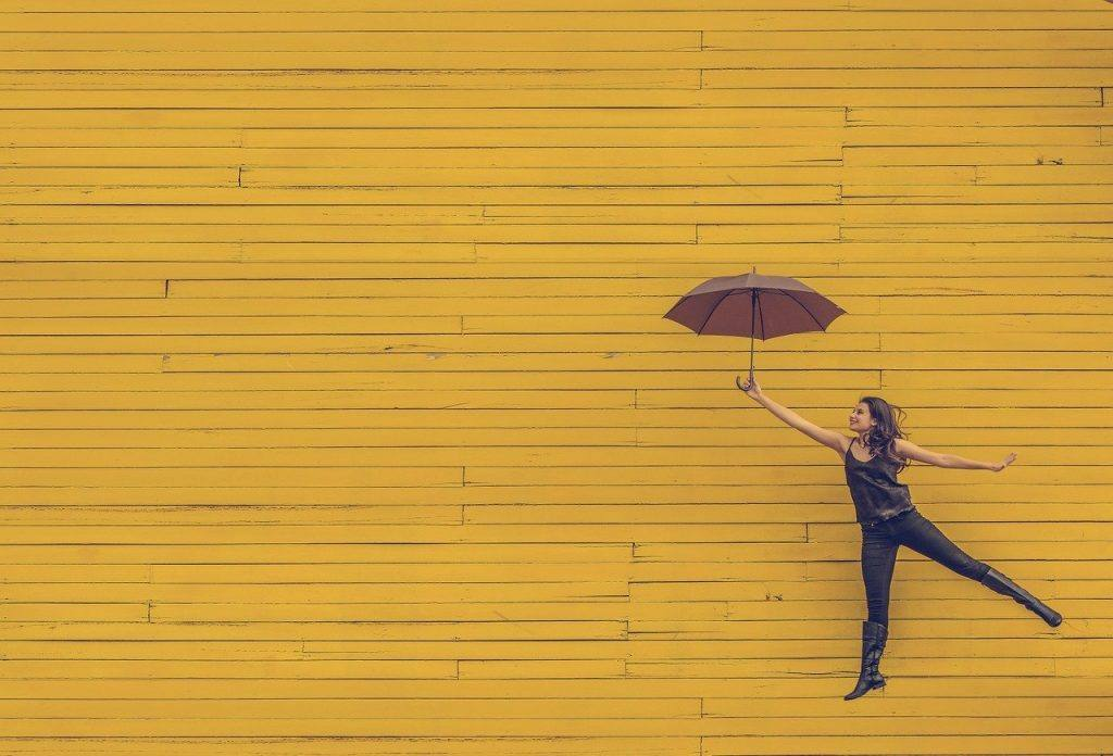 Photo of a woman floating on an umbrella in front of a yellow wall to represent a sense of growing more awake and vivid in sobriety.