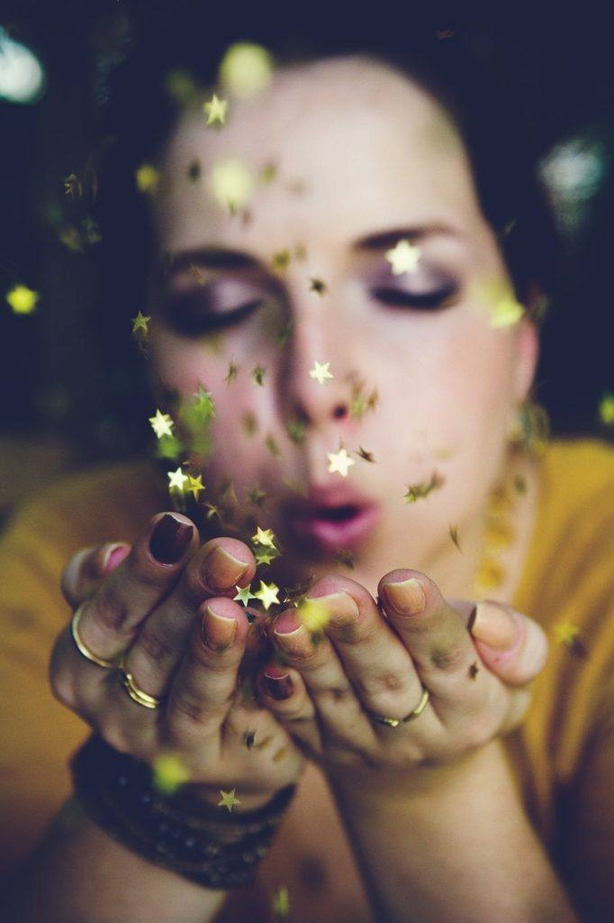 Woman blowing gold stars - 16 lessons I learned when I stopped drinking