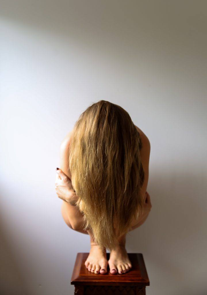 Woman hiding behind hair- drinking to be invulnerable