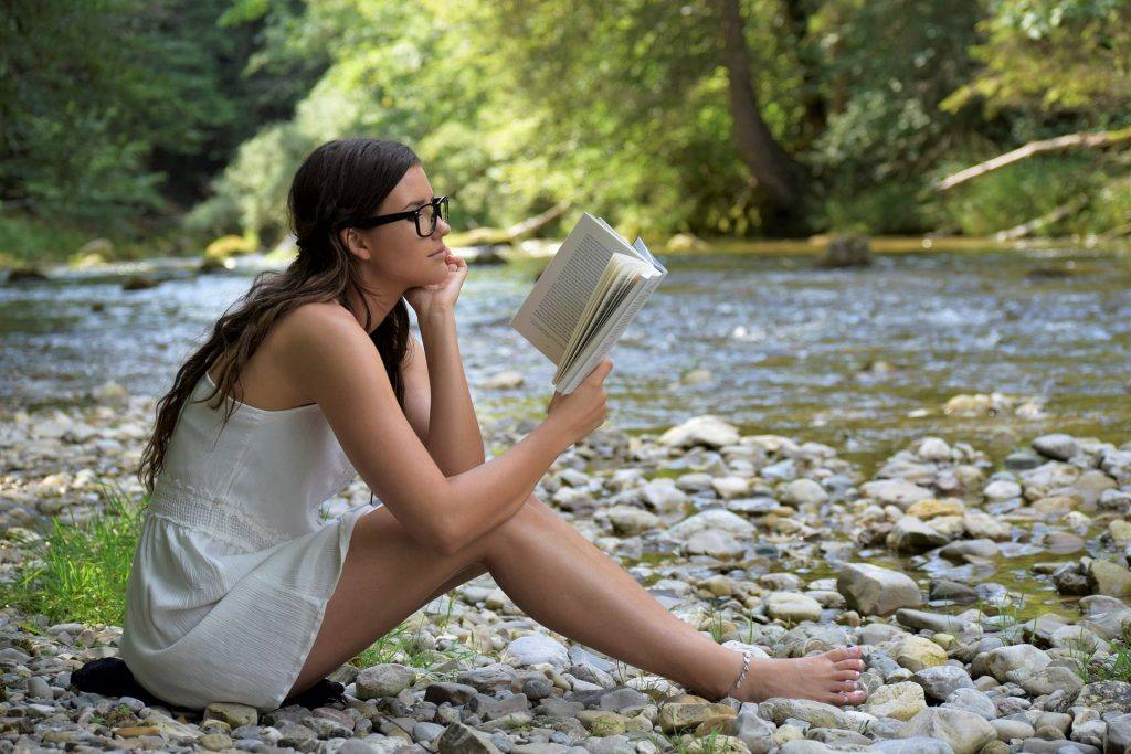 Woman reading book on  I can't be an alcoholic! I didn't hit rock bottom!