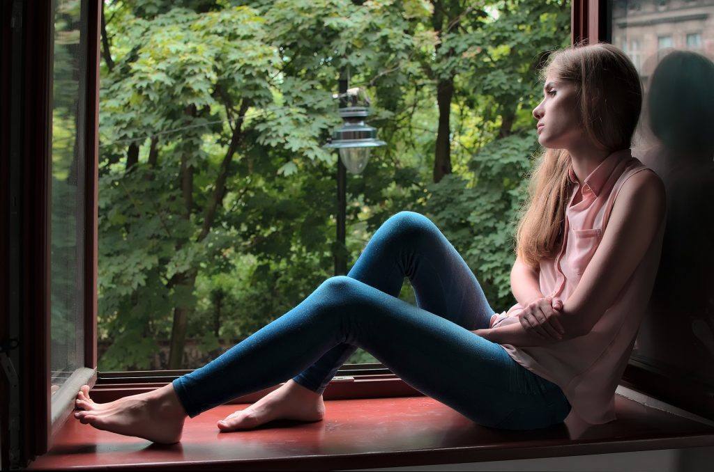 Woman sitting in window Dealing with alcohol cravings in early sobriety