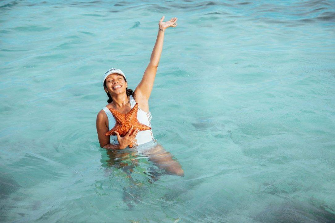 Smiling woman in water with Star fish Dry July 2020, Day 5 Alcohol-Free Inspiration
