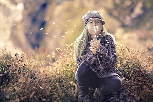 Young woman blowing dandelion fluff- my inner child evolving in sobriety