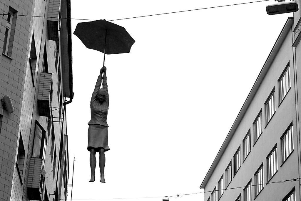 Woman hanging fron clothes line on umbrella- Anxiety caused by lack of self discipline and self care