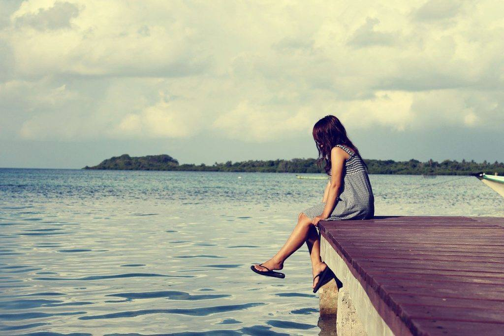 Woman sitting on dock - alcohol lonliness and living sober
