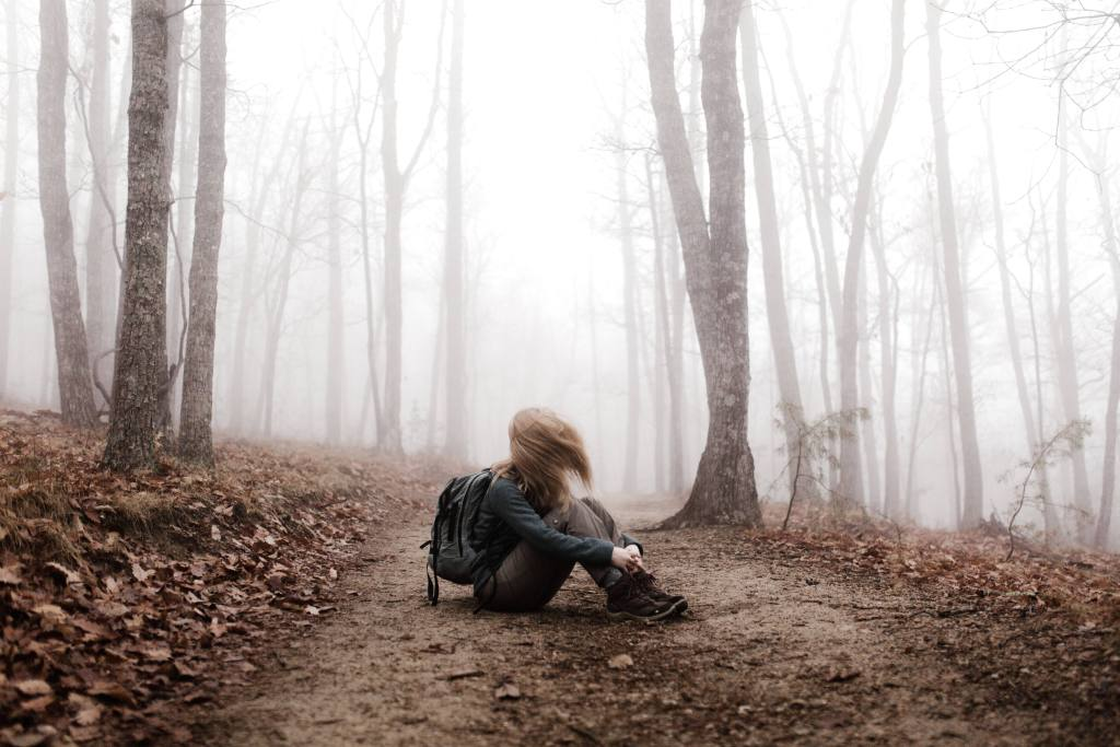 woman sitting on Trail in forest after slipping while trying to stay sober