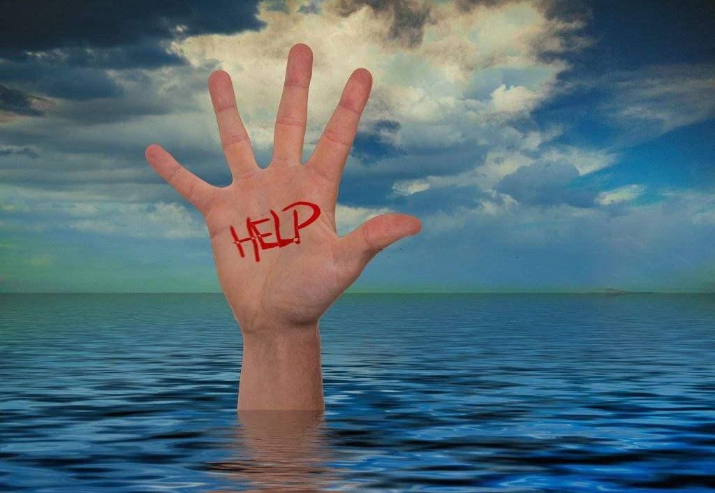 Hand reaching for help to stop drinking and stay sober with an online community