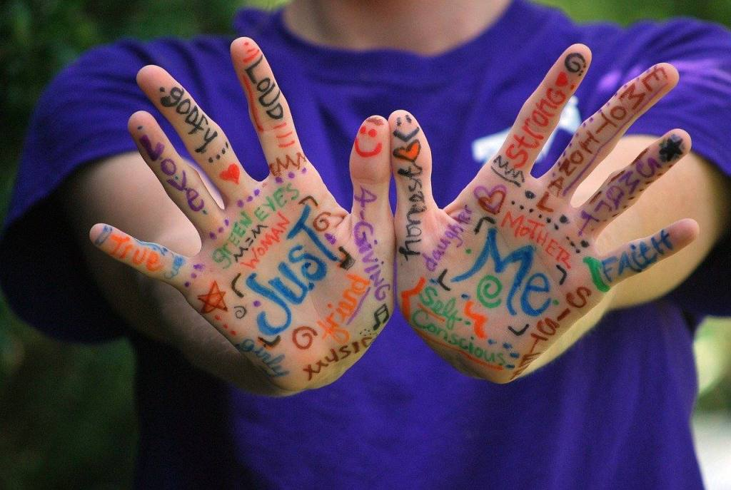 Hands of woman painted with positive things that she's found since she stopped drinking with an online community