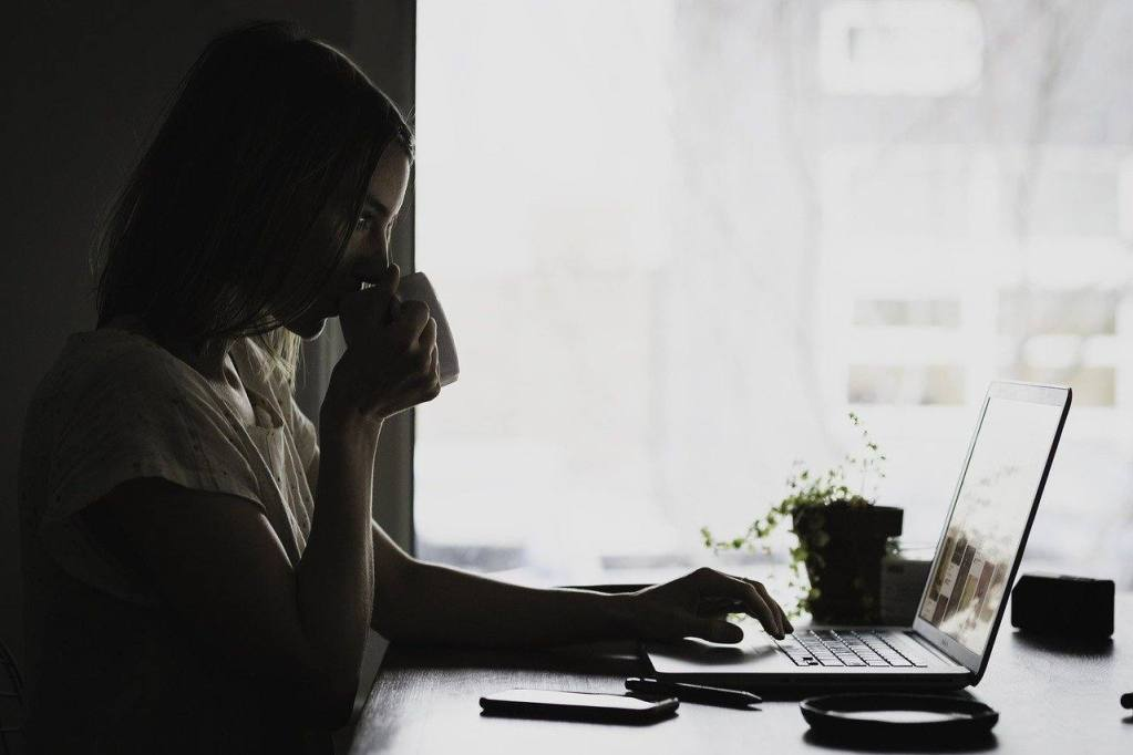 Woman at computer writing about first 30 days sober or early sobriety