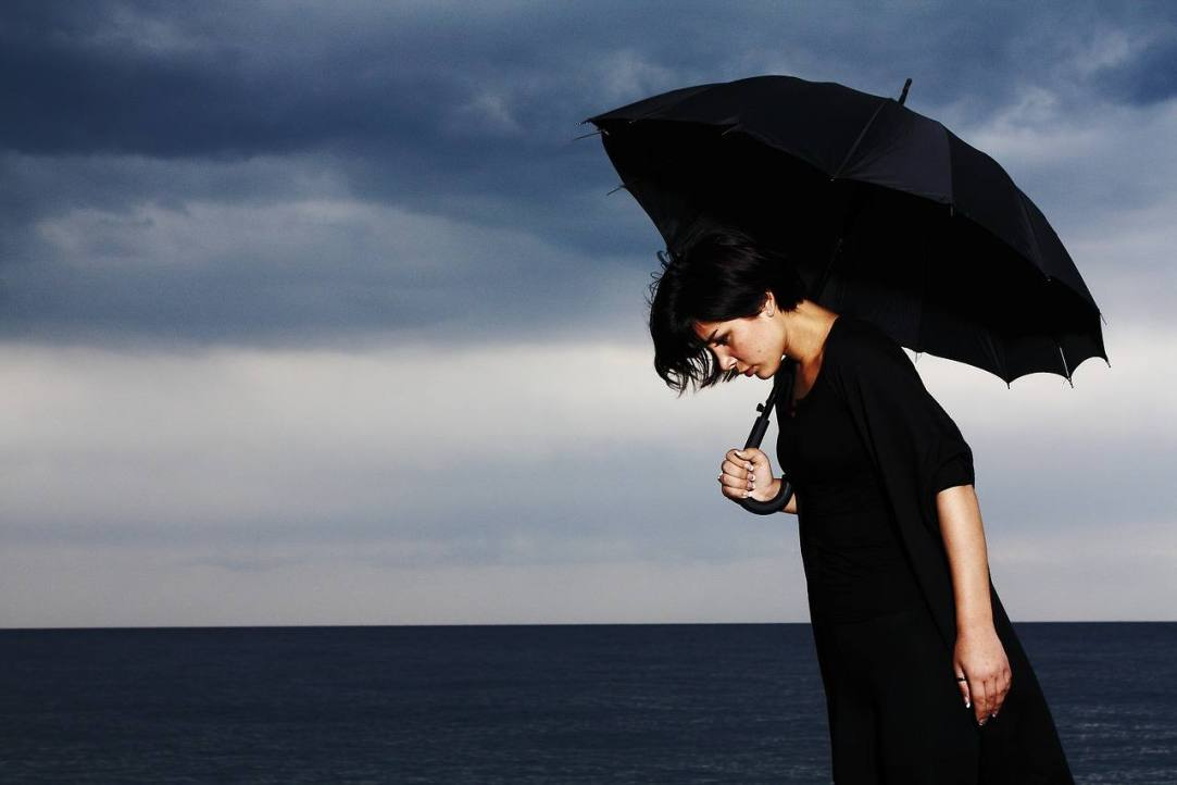 Woman under Black Umbrella - Ome day at a time determination