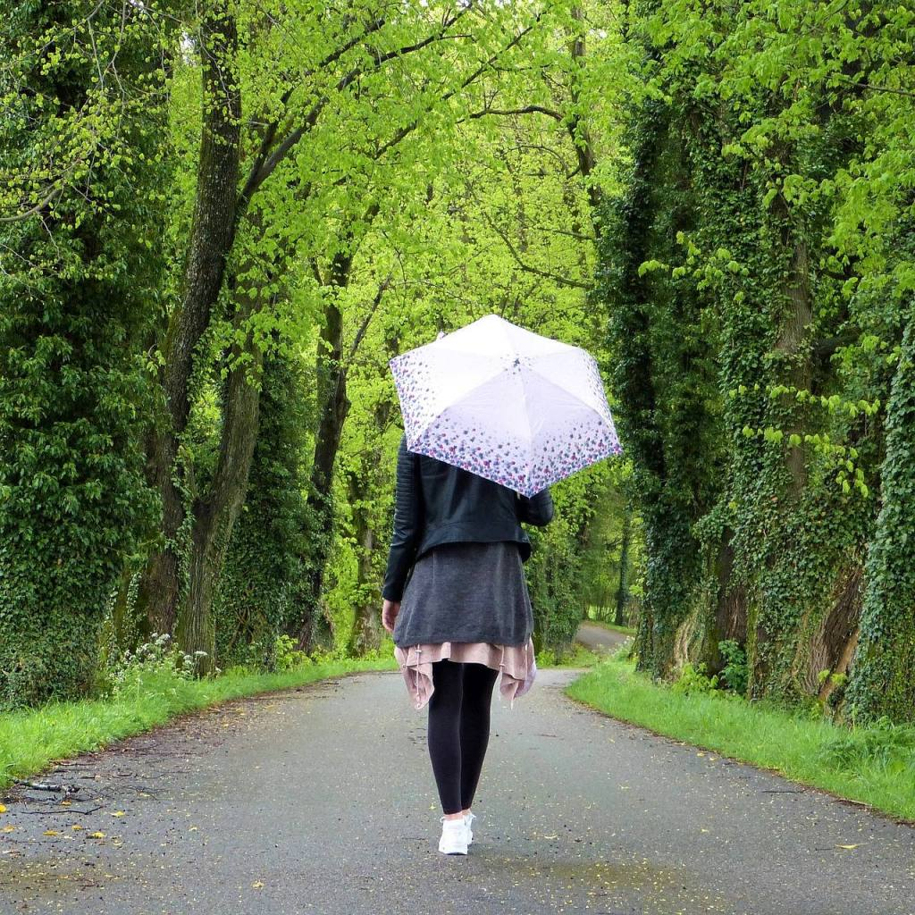 Woman in forest with umbrella - one day at a time six months sober