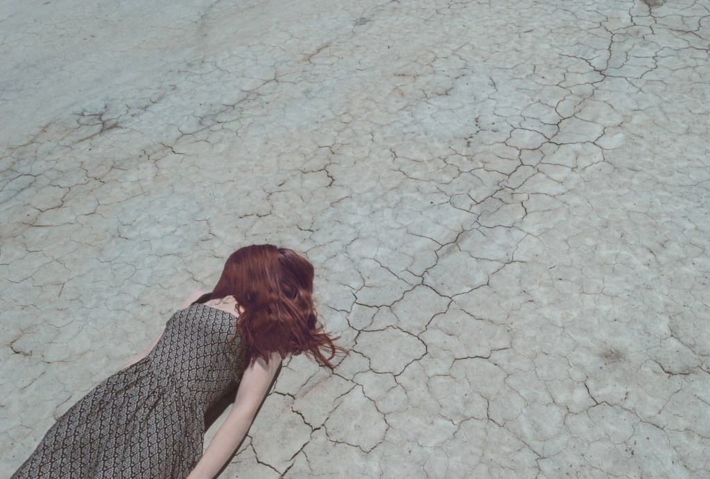Woman laying on Cracked ground Your Scars are Beautiful - Moving Toward Emotional Sobriety with Inspiration from Kintsugi