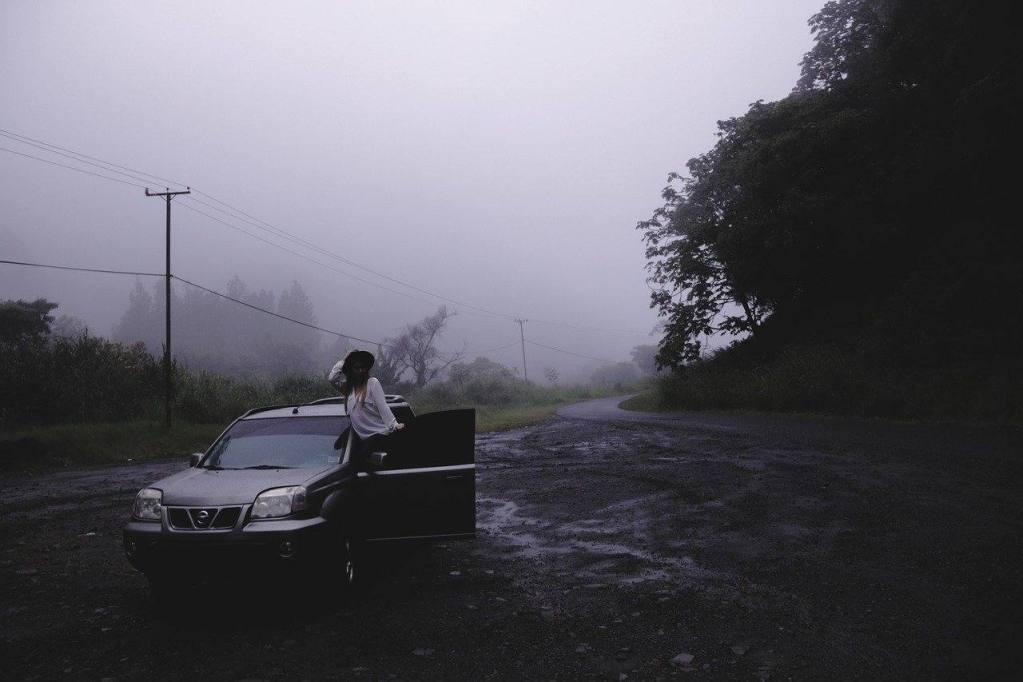 woman with broken down car on dark road- beginning of sobriety road trip- stuck in oblivion
