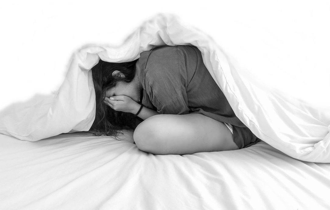 woman hiding under covers anxiety alcohol and sobriety