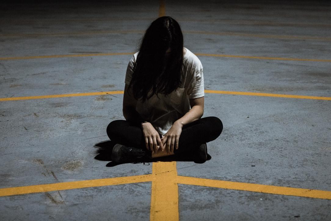 Woman sitting hiding behind hair paranoia