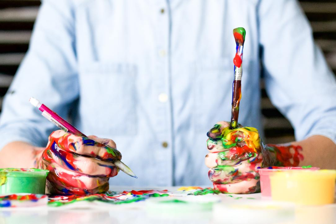 Person with paint on hands holding brush and pencil- living sober is an art that takes practice